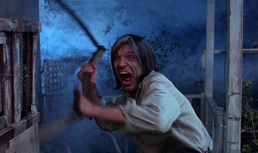 Neville Brand handles a scythe in Tobe Hooper's Eaten Alive